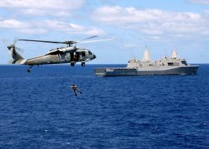 MH-60S y nadador de rescate en adiestramiento. Al fondo, el USS Mesa Verde (LPD-19)
